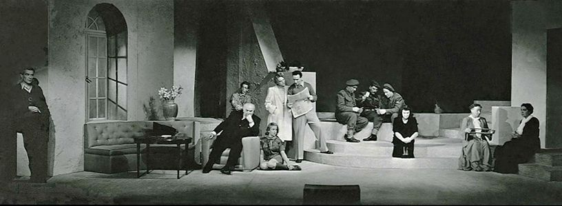 The opening stage of Antigone. Creon is in his armchair and Ismene at his feet; Antigone is in the center and Eurydice is knitting on the right, throughout the entire play, until her death -- the nurse holding the yard between her hands.