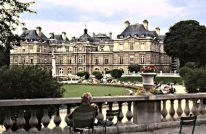 A lone lady resting in front of le Palais du Luxembourg with gardens. The palace dates from the 17th century, and it is the seat of the Senate.