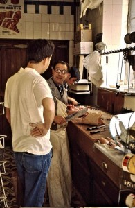 John is discussing - maybe a recipe - with his butcher. His store is long gone.