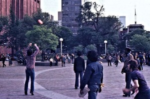 Frisbee players on Washington Square, whcih is surrounded by the numerous New York City University buildings.