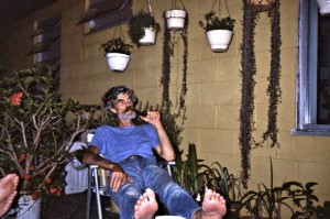 Girv smoking his pipe on his sundeck, surrounded by plants; hibiscus and others.